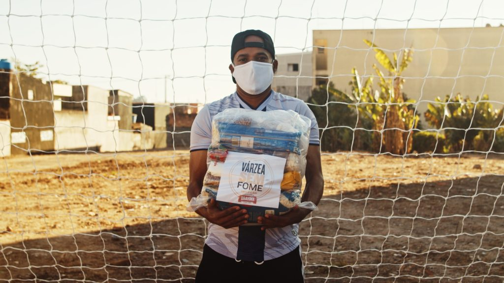 Jogador do futebol de várzea segura cesta básica que será doada pela Brahma às famílias.