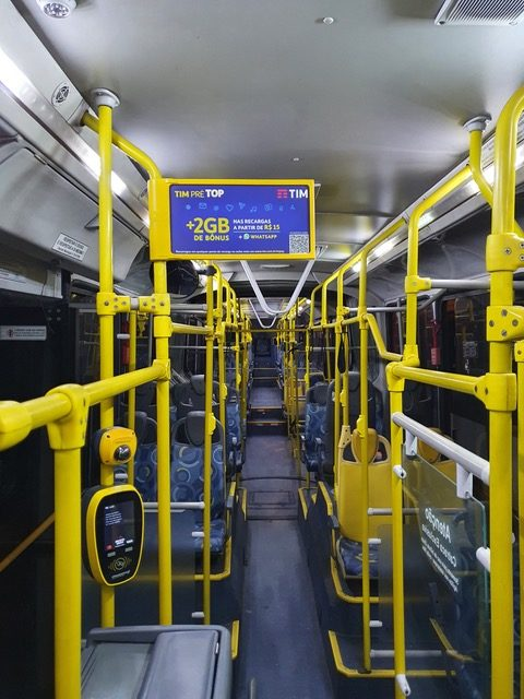 Foto mostra o interior do ônibus com um painel B-AIR posicionado acima da catraca
