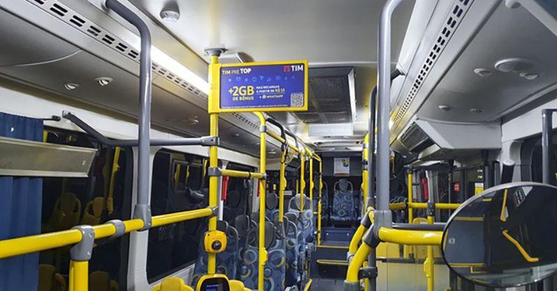 foto do interior de um ônibus exibindo propaganda da TIM em um painel B-AIR sobre a catraca