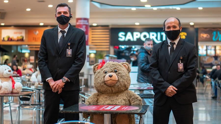 Urso sentado na mesa com seguranças shopping mueller joinville