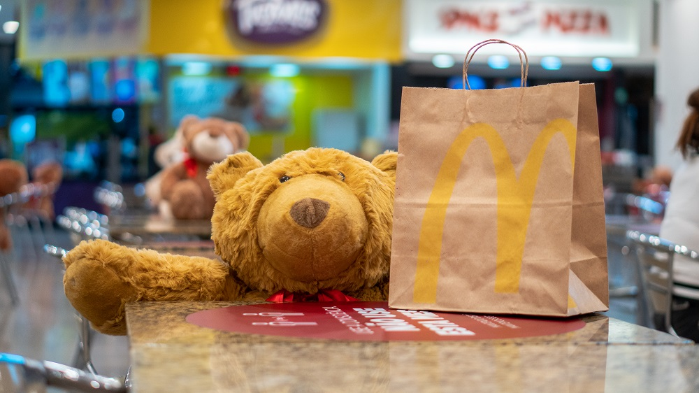 Urso sentado na mesa com sacola do McDonald's shopping mueller joinville