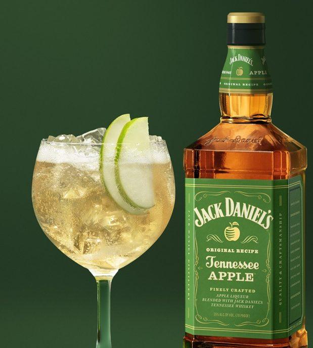 Taça de Jack Daniel's com tônica, suco de limão e rodelas. A garrafa da bebida está ao lado.
