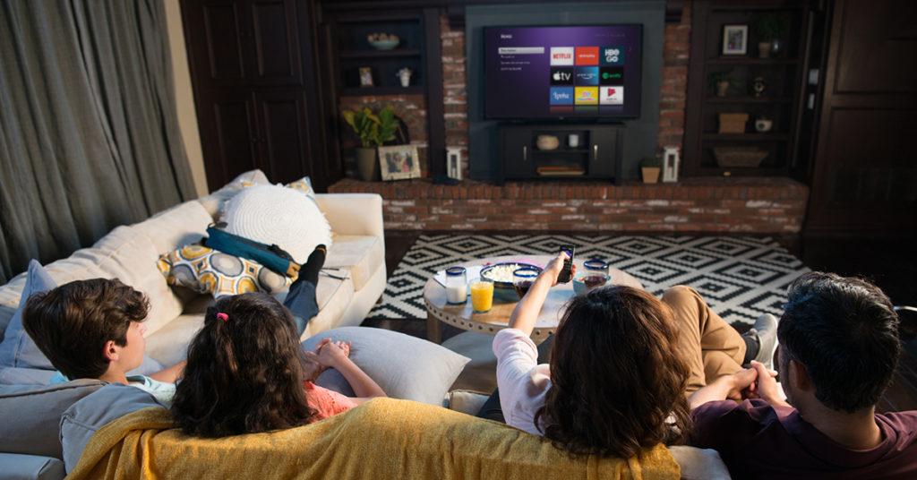 Família assiste à Roku TV na sala.
