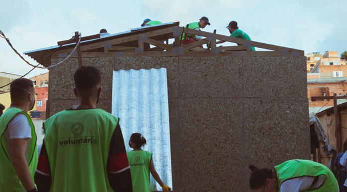 Voluntários ajudando na construção dos telhados feitos a partir de telhas recicladas das caixas de sucos Do Bem.