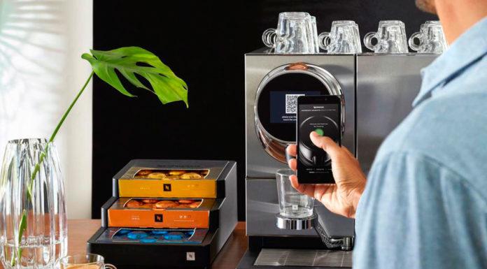 Um homem ativando a nova máquina de café da Nespresso com um celular.