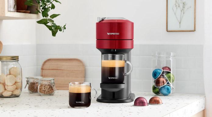 Nova máquina tecnológica da Nespresso. A foto apresenta uma mesa com a máquina, cápsulas, duas xícaras de café e doces pela mesa.