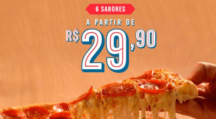 Foto de divulgação da promoção de pizza por R$ 29,90 da Domino's. A foto apresenta uma pessoa pegando um pegado de pizza de Pepperoni, e acima está escrito