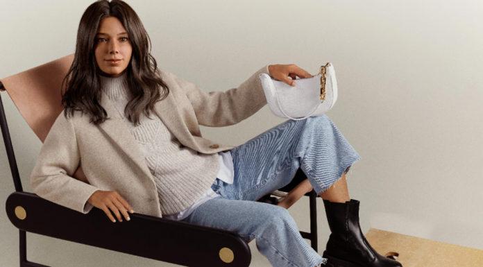 Imagem de Rennata, nova influenciadora virtual da Renner, sentada em uma cadeira e vestindo casaco e blusa tricô cor clara, camiseta branca, calça jeans pantacourt, bota preta tratorada e uma bolsa baguete com detalhe em corrente dourada