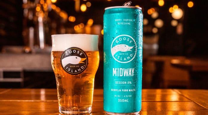 Goose Island Midway lata ao lado de um copo com cerveja, em um balcão de bar, ao fundo luzes com um ambiente desfocado.