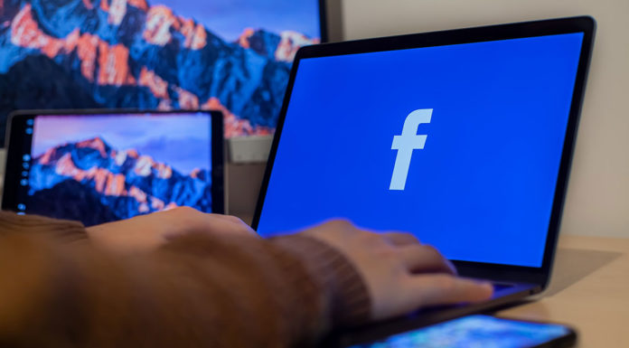 A foto apresenta um computador abrindo o Facebook, que anunciou que a distribuição de posts problemáticos irá diminuir.