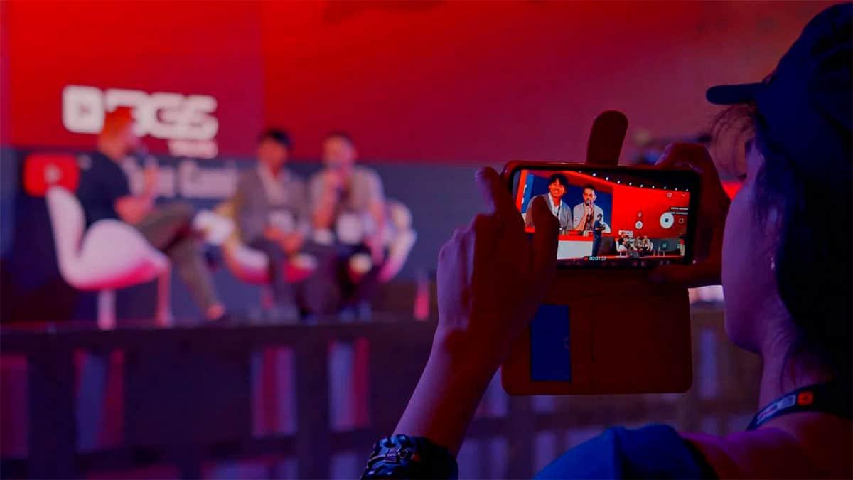 A foto apresenta uma menina tirando uma fotografia de um painel que aconteceu em edições passadas da Brasil Game Show, para representar uma das atrações da programação do evento.