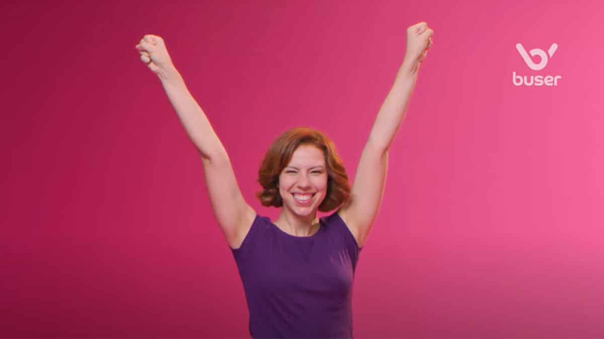 A foto apresenta um frame da campanha de posicionamento da Buser, em que mostra uma mulher sorrindo com os braços levantados, ao lado do logo da marca.