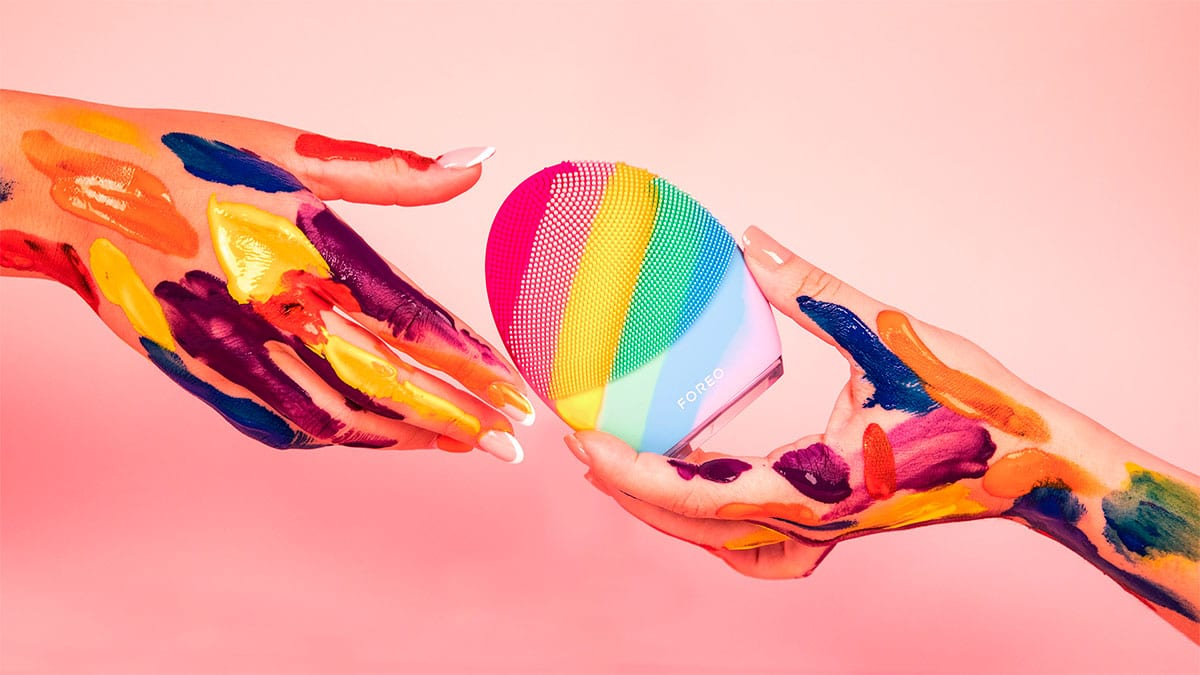 A foto da campanha para celebrar o orgulho LGBTQIAP+ da FOREO apresenta um fundo rosa, e duas mãos na frente com várias pinceladas coloridas, passando a YOUnique LUNA de uma para a outra.