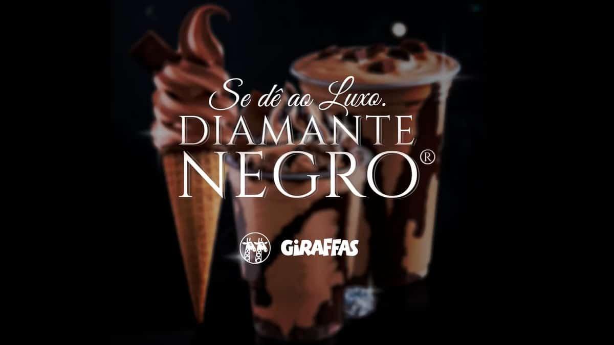 A foto apresenta as sobremesas de Diamante Negro do Giraffas ao fundo e desfocado, com uma frase na frente escrito: Se dê ao luxo, com o logo das marcas.