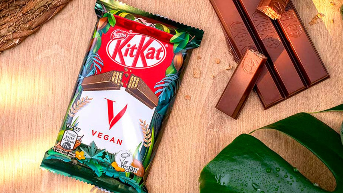A foto apresenta uma embalagem do KitKat V em uma mesa de madeira, ao lado do chocolate vegano desembalado e algumas plantas ao redor.