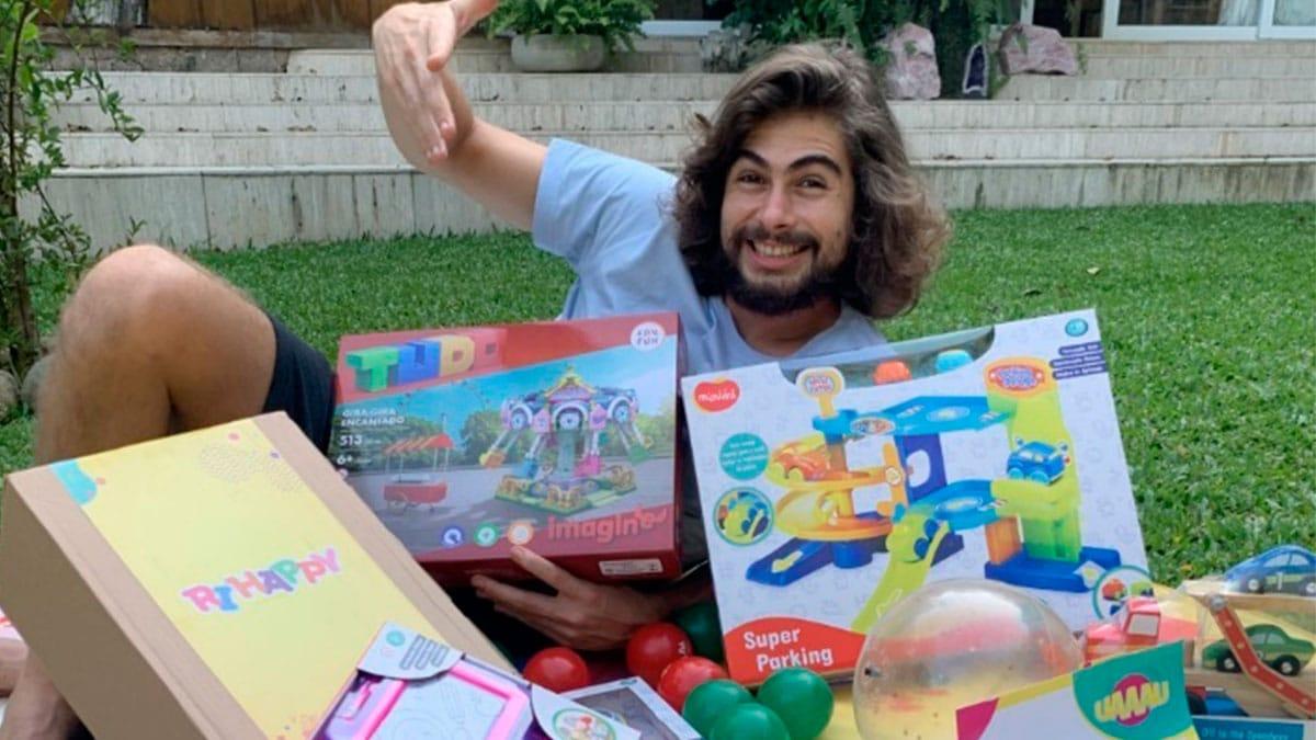 A foto apresenta o ator Rafa Vitti na grama deitado e sorrindo, com a mão levantada, junto com vários brinquedos do Grupo Ri Happy.