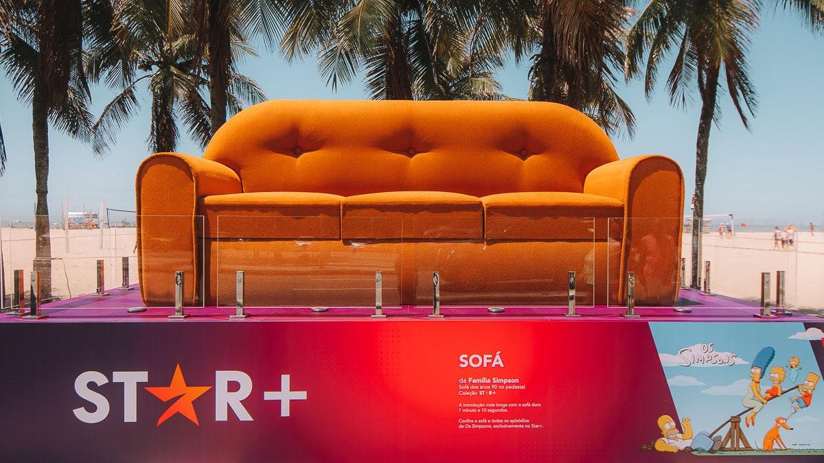 A foto apresenta a escultura do sofá de Os Simpsons que a Star+ colocou na Orla de Copacabana, em meio a vários coqueiros.